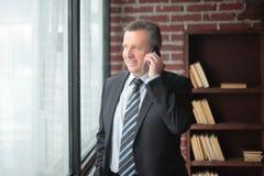 微笑的商人谈话在电话 免版税库存图片