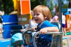 微笑的公平的儿童男孩乘坐的娱乐乘驾 免版税图库摄影