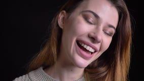 得到害羞微笑和笑在照相机前面的年轻女性白种人女性面孔特写镜头画象  股票录像