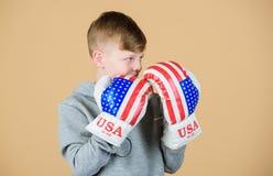 往胜利 确信对他的力量 开始把事业装箱 男孩运动员穿戴与美国旗子的拳击手套 库存照片