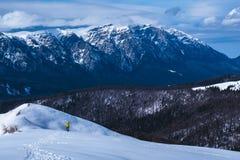 徒步旅行者在山的心脏在与伟大的冬天山景后边 免版税图库摄影