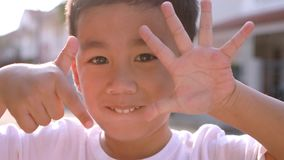 快乐的亚裔孩子的接近的面孔递使用第一到十 股票录像