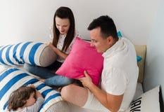 快乐的有孩子和的父母在床上的枕头战在家 免版税库存图片