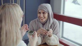 快乐的阿拉伯妇女是她咖啡馆的白肤金发的朋友妇女听的故事  股票视频