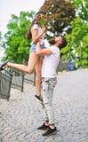 培养女朋友的人 浪漫日期步行 愉快看她 当她拿着花时,供以人员运载的女朋友在手上 库存图片