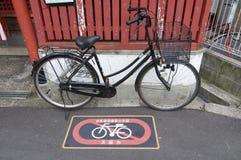 在一个停放的禁令停放的黑自行车在大阪,日本签字 免版税库存图片