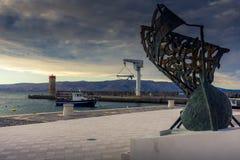在一个口岸的一条小船与一艘帆船的雕象在前景的 免版税库存图片