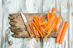 在一个切板的切的红萝卜有刀子的 库存图片