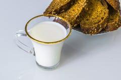 在一个杯子的牛奶在桌上用面包,烘干 图库摄影