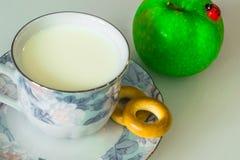 在一个杯子的牛奶在桌上用面包,烘干 库存照片