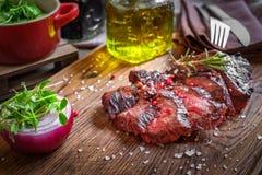 在一个木板的烤牛后腹肉排 库存图片