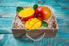 在一个木箱的著名亚尔方索芒果切片在木背景,顶视图 库存图片