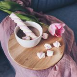 在一个灰色沙发的桃红色郁金香,白色咖啡 免版税库存图片