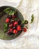 在一个灰色碗,顶视图的新鲜的红色樱桃,在白色背景 免版税库存照片