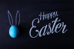 在一个黑板的一个蓝色被绘的复活节彩蛋有被按的耳朵的看起来象兔子 文本,复活节快乐 免版税库存图片