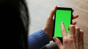 在一个黑智能手机的色度关键或绿色屏幕在有穿着考究的修指甲和黑色头发的女性手上在 股票录像