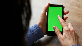 在一个黑智能手机的色度关键或绿色屏幕在有穿着考究的修指甲和黑色头发的女性手上在 股票视频