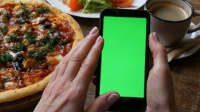 在一个黑智能手机的色度关键或绿色屏幕在有穿着考究的修指甲的女性手上在背景大 影视素材