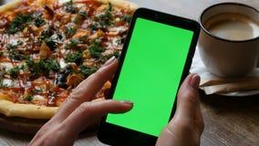 在一个黑智能手机的色度关键或绿色屏幕在有穿着考究的修指甲的女性手上在背景大 股票录像