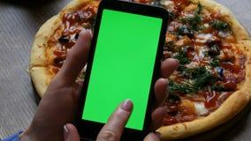 在一个黑智能手机的色度关键或绿色屏幕在有穿着考究的修指甲的女性手上在背景大 股票视频