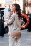 在一件丝绸女衬衫的轻的毛线衣打扮的时髦的女孩和在街道的轻的长裤姿势 图库摄影