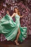 在一件薄菏色礼服的美女模型在开花的春天背景 有一种惊人的构成和发型的秀丽女孩 图库摄影