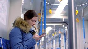 在一块空的地铁的妇女乘驾和浏览在她的智能手机 侧视图 股票视频