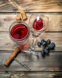 在一块玻璃的红酒用葡萄和拔塞螺旋 库存照片