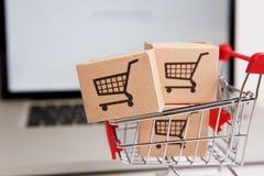 在一小手推车的许多纸箱在膝上型计算机键盘 关于消费者能买的网络购物的概念 免版税库存图片