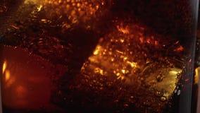 在一杯的浮动冰块可乐-宏观射击的关闭在慢动作 影视素材