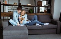 在一起使用在沙发的蓝色牛仔布布料的甜年轻夫妇 免版税库存照片