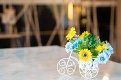 在一辆白色自行车的美丽的花在木桌上 在白色自行车的美丽的花在木桌上 安置文本 免版税库存照片