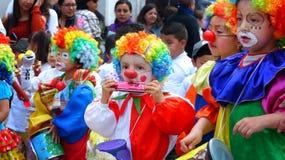 在五颜六色的服装打扮的小组小孩作为小丑在游行 免版税图库摄影