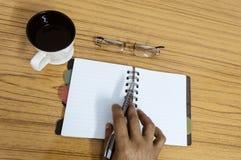 在他的日志的商人文字 有空白页的开放笔记本在咖啡和镜片旁边在木桌上 事务 免版税库存照片