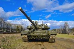 在伪装的俄国装甲的坦克反对一蓝色天空蔚蓝 枪在上面邪恶看 库存照片
