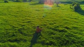 在体育瑜伽人的低空辐形飞行完善的绿草的 在山的日落 股票录像