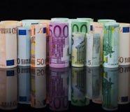 在卷的欧洲纸币在与反射的黑背景 免版税库存图片