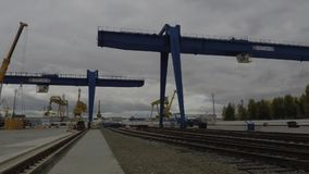 在后勤运输公司的大桥式起重机在灰色,多云天空背景 桥式起重机、卡车起重机和人们 影视素材
