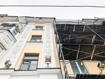 在大厦的门面的修理工作在木脚手架,结构,老房子的恢复帮助下的 库存照片