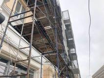 在大厦的门面的修理工作在木脚手架,结构,老房子的恢复帮助下的 免版税库存照片