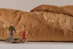 在大长方形宝石面包和计数硬币旁边的微型妇女和人形象身分 浅景深背景 家庭 库存图片