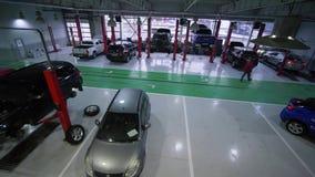 在大,工作期间汽车服务站,许多汽车在推力和在地板上在修理期间和技术员走 股票录像