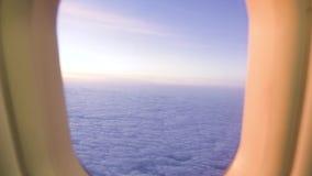 在天空视图的白色云彩从飞机窗口,当金黄日出时 从窗口飞行的飞机日落的看法在多云天空 股票视频