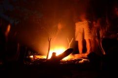 在夜森林人民的野餐在火附近站立 免版税库存照片