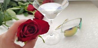 在女性手指的一朵红色玫瑰反对宽藤玻璃 图库摄影