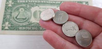 在女性放置的以色列锡克尔四枚硬币移交一美国美元 免版税库存图片