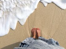 在女性腿和脚的顶视图在海滩 免版税库存图片