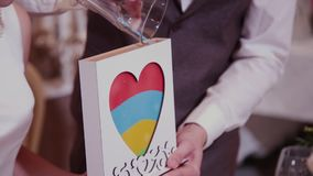 在婚礼的沙子仪式 新郎关闭玻璃船管充满不同颜色沙子在婚礼 股票录像