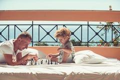 在家下与爸爸-年轻男孩和他的父亲的棋 库存图片