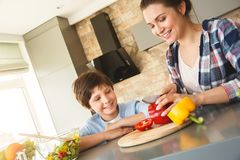 在家一起站立在厨房儿子的家庭看切开菜的母亲快乐 图库摄影
